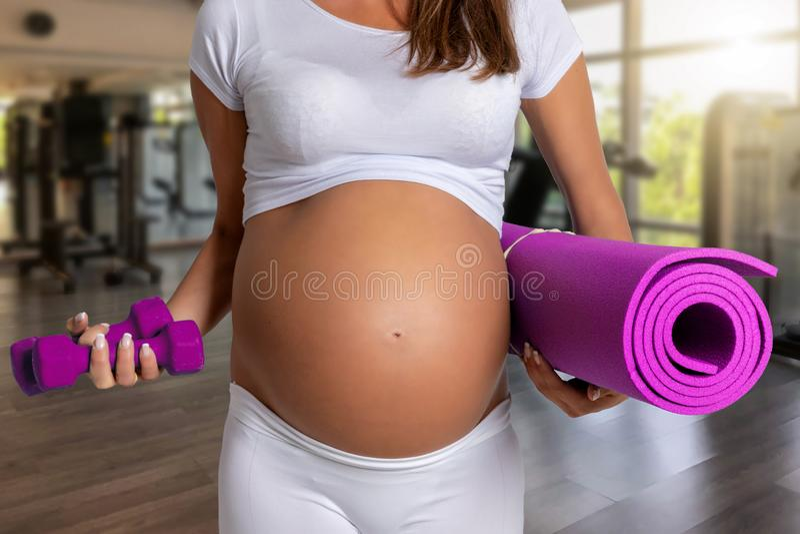 Беременная женщина в спортзале готовом для разминки стоковая фотография