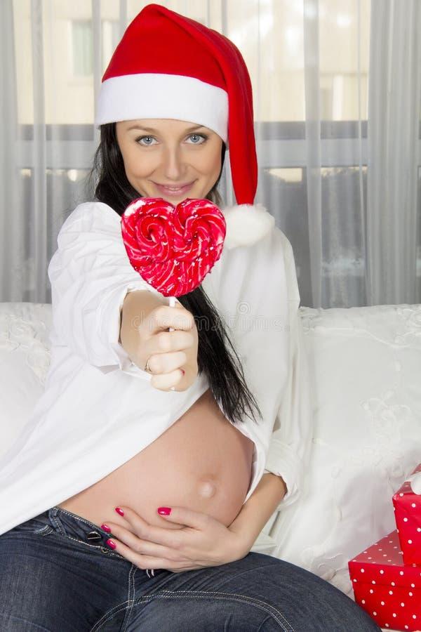 Беременная женщина в шляпе santa стоковое изображение rf