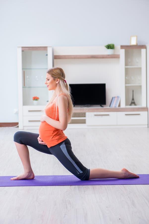 Беременная женщина делая тренировку спорта дома стоковое фото