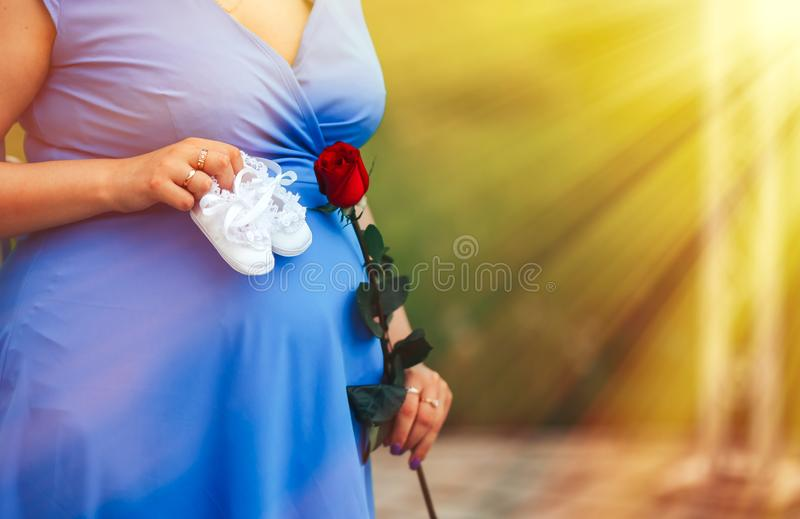 беременная женщина держа белое baby& x27; bootee s нося в голубом платье над предпосылкой природного парка на заходе солнца стоковые изображения rf
