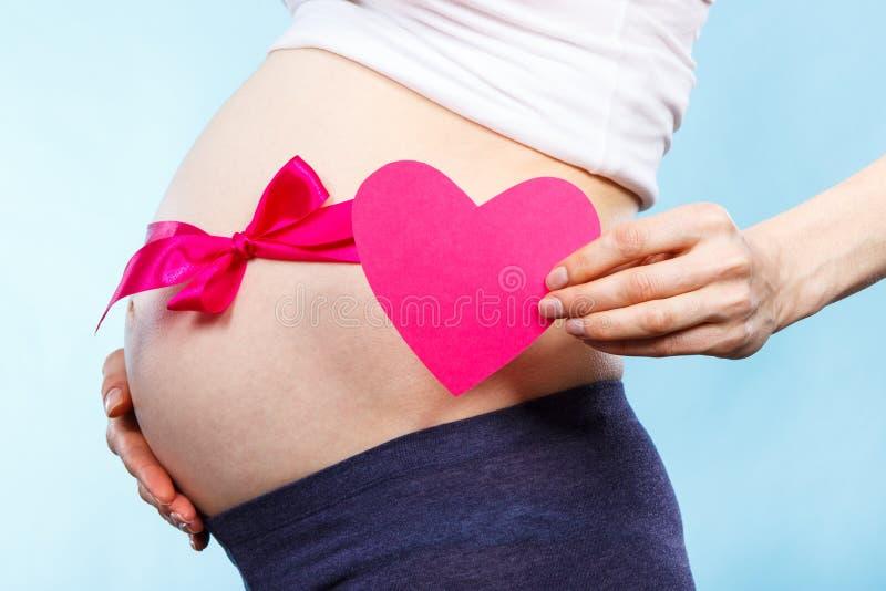 Беременная женщина держа сердце и касаясь ее животу с розовой лентой, концепцией предпологать для newborn девушки стоковая фотография rf