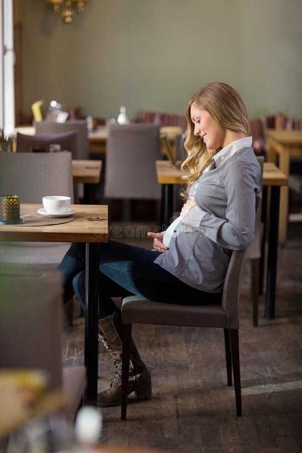 Беременная женщина держа ее живот на кафе стоковое фото
