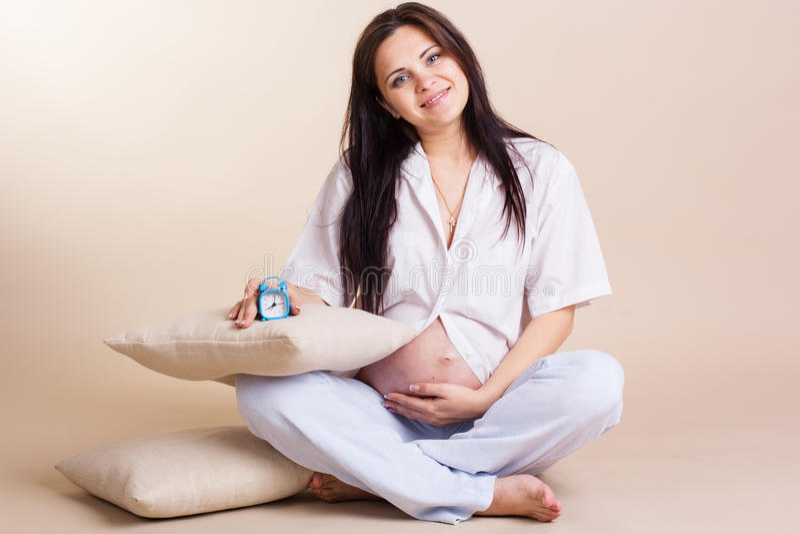 Беременная женщина держа живот в белой рубашке стоковое фото