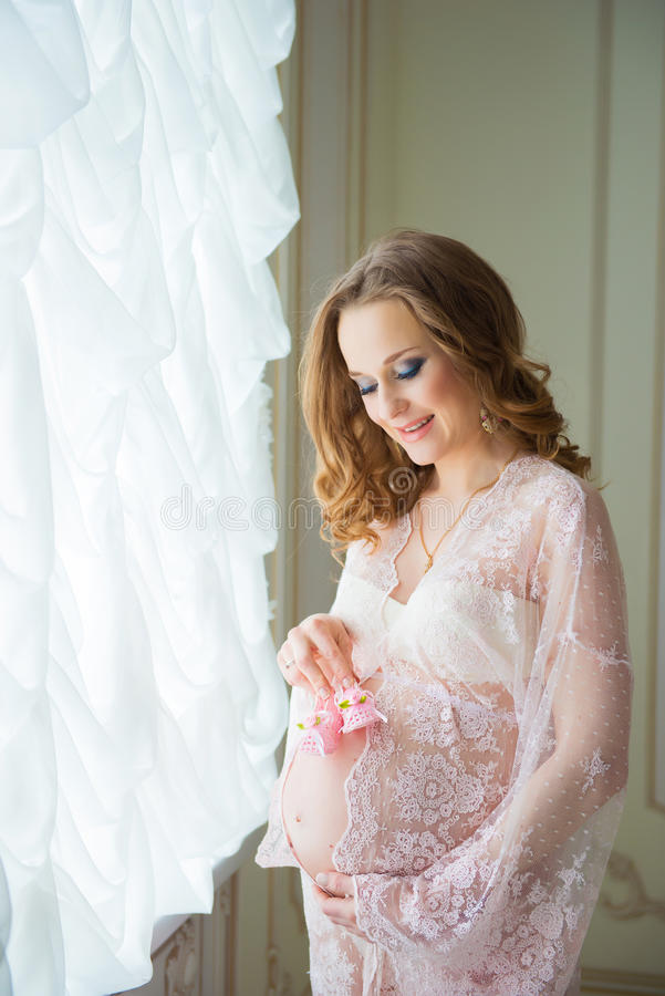 Беременная женщина держа розовые ботинки младенца на ее животе стоковые фото