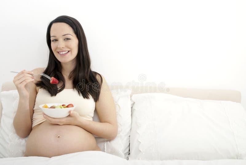 Беременная женщина есть завтрак стоковое фото rf