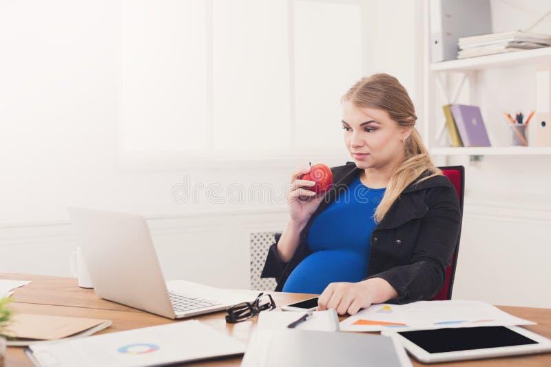 Беременная женщина есть яблоко в космосе копии в деле стоковое изображение rf