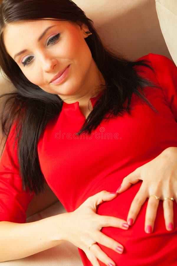 Беременная женщина делает форму сердца над животом стоковое фото