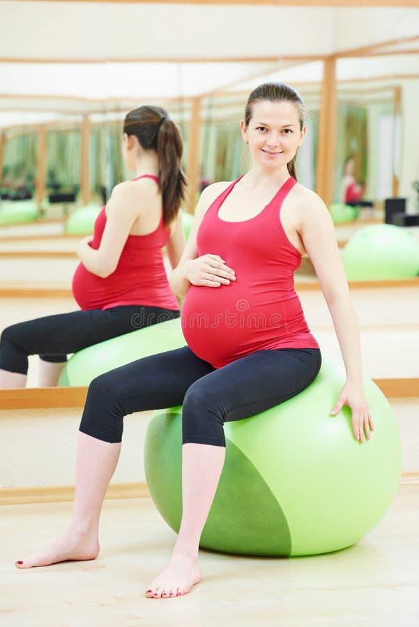 Беременная женщина делая тренировку шарика фитнеса стоковое изображение rf