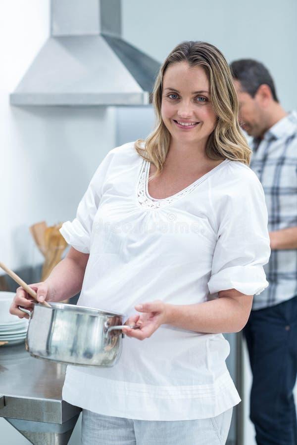 Беременная женщина занятая в кухне стоковые изображения