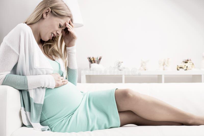 Беременная женщина имея боль в животе стоковые фотографии rf