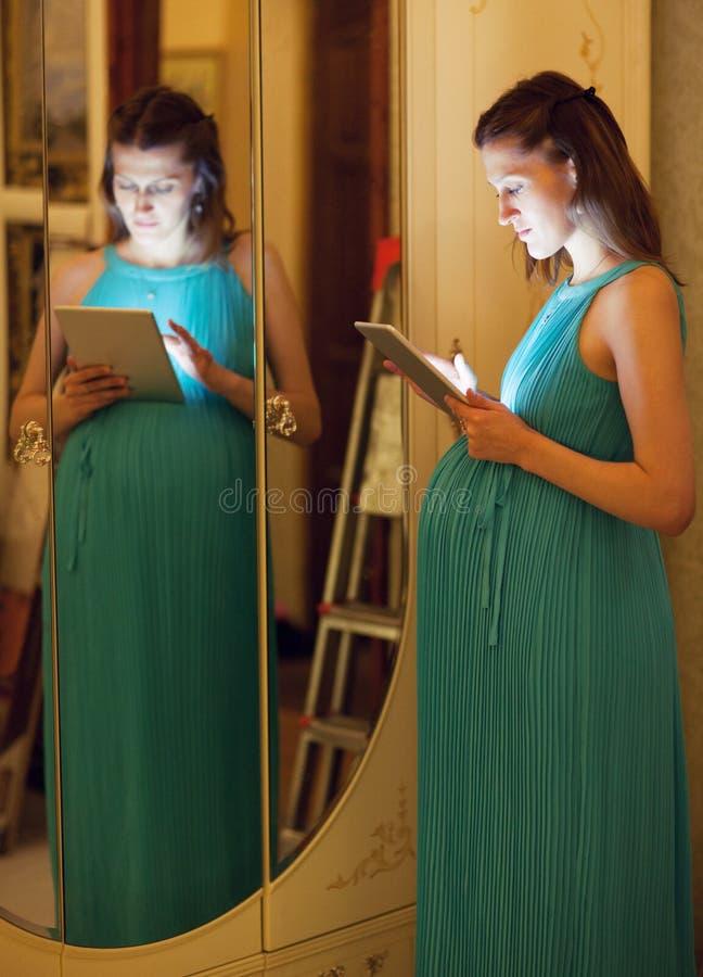 Беременная женщина используя таблетку дома стоковое изображение rf