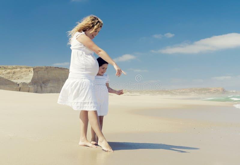 Беременная женщина и ее дочь на пляже стоковые фотографии rf