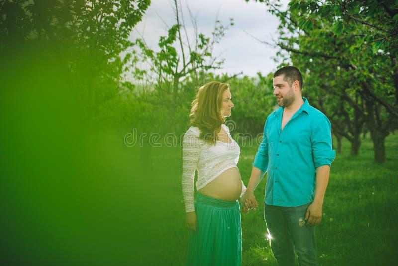 Беременная женщина и ее супруг в зеленом лесе стоковая фотография rf
