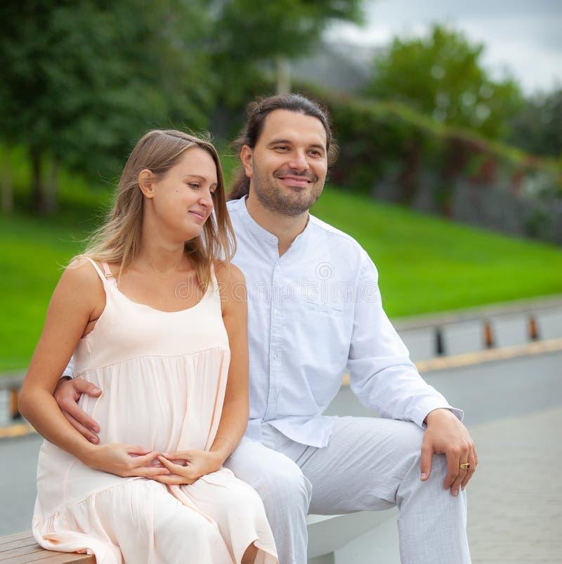 Беременная женщина и молодой отец на улице стоковое изображение