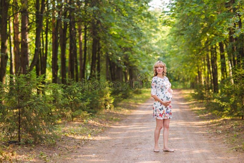 Беременная женщина идя в парк и обнимая ее беременный живот стоковые изображения
