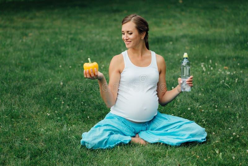 Беременная женщина йоги с бутылкой воды и болгарского перца, в положении лотоса парк, трава внешний, лес стоковое фото