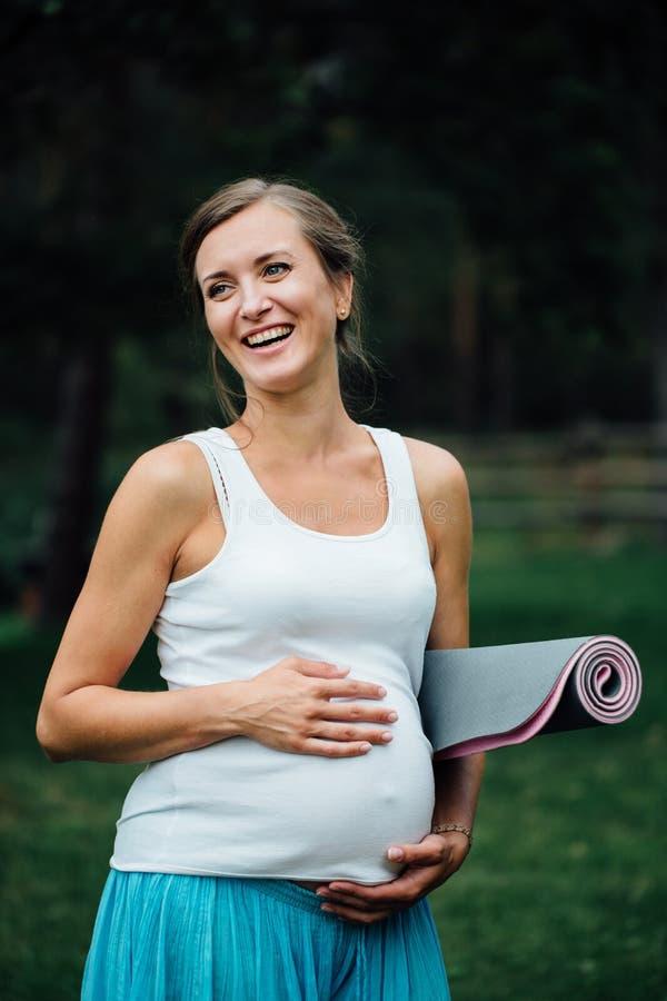 Беременная женщина йоги с портретом циновки в парке на траве, дышать, протягивая, статика внешний, лес стоковое фото