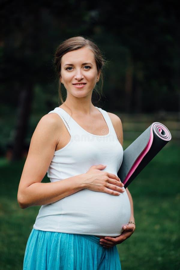 Беременная женщина йоги с портретом циновки в парке на траве, дышать, протягивая, статика внешний, лес стоковое изображение rf