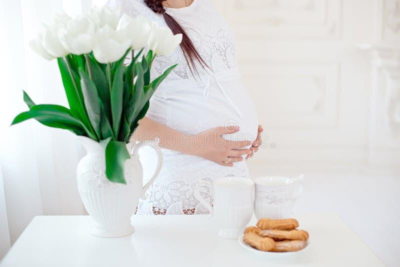 Беременная женщина конца-вверх в белой комнате стоковое изображение