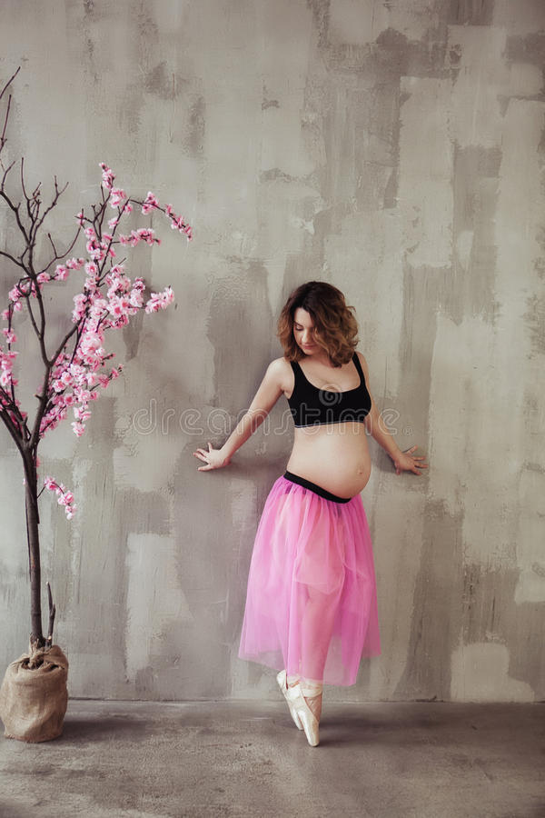 Беременная женщина концепции фитнеса и спорта беременности счастливая около розового дерева Сакуры артист балета на серой предпос стоковое фото rf