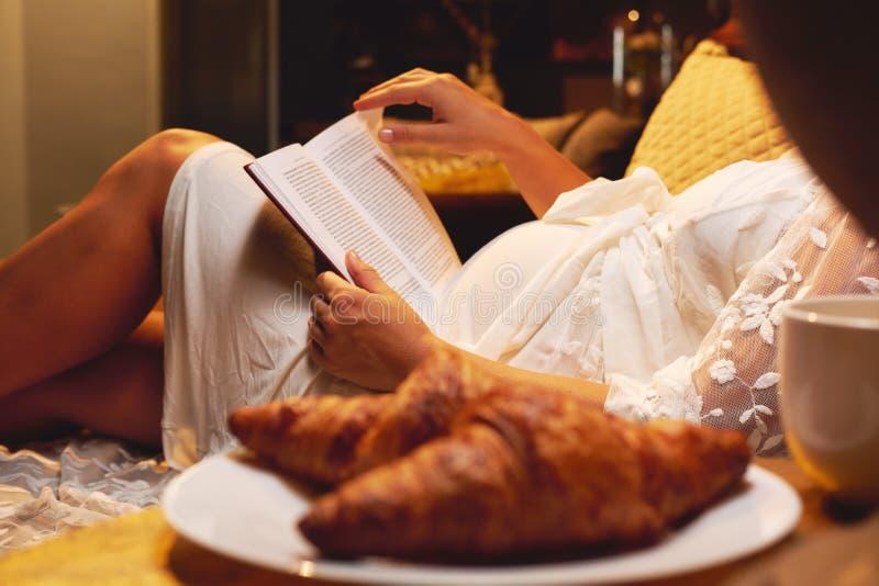 Беременная женщина лежа на кровати на спальне и читая книгу о материнстве или chicklit, романе женщины дома стоковое фото
