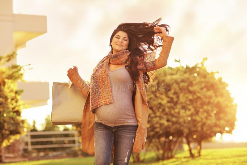 Беременная женщина наслаждаясь ходить по магазинам стоковая фотография rf