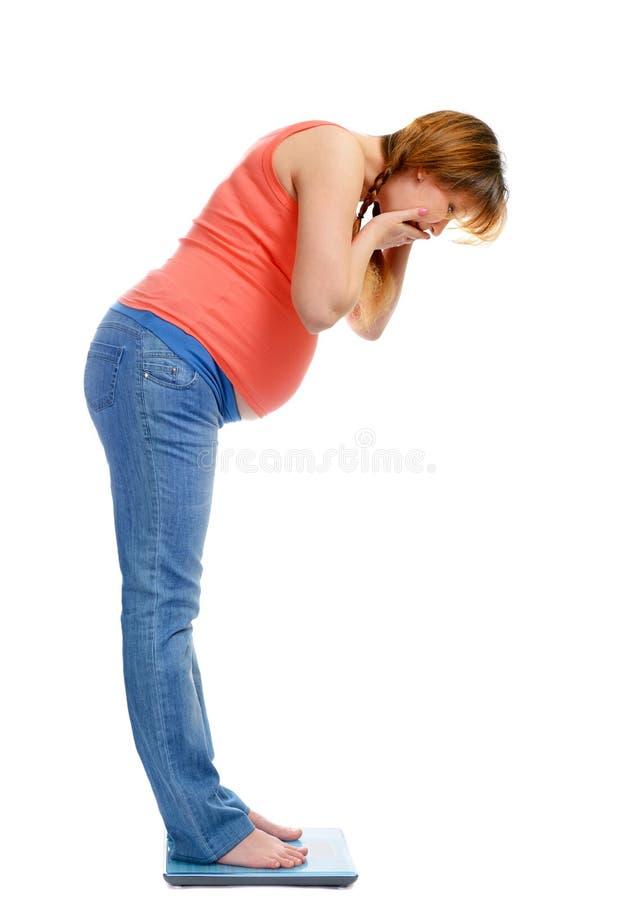 Беременная женщина на масштабах удивленная своим весом стоковые фотографии rf