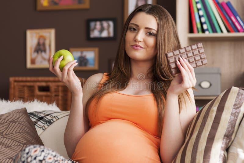 Беременная женщина не может решить стоковое изображение rf