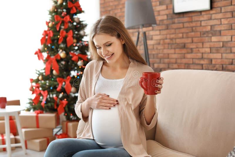 Беременная женщина около рождественской елки дома стоковые изображения rf