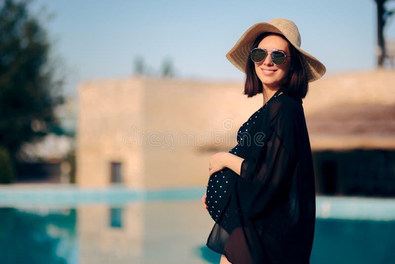 Беременная женщина ослабляя на каникулах бассейном стоковое изображение rf