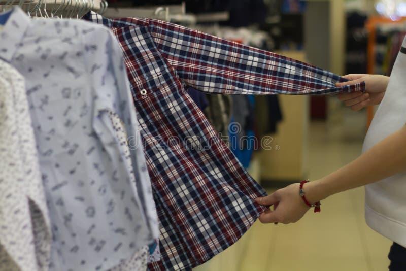 Беременная женщина покупок, ручная рубашка в клетке, ребенок стойки просмотра в магазине стоковые изображения rf