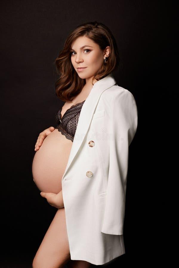 Беременная женщина представляя на черной изолированной предпосылке стоковое фото