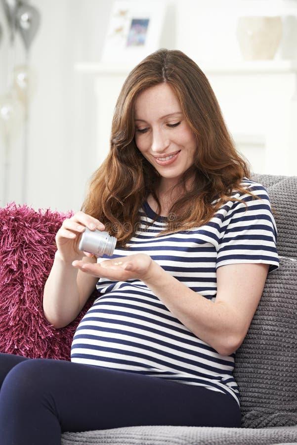 Беременная женщина принимая таблетки фолиевой кислоты стоковые изображения rf