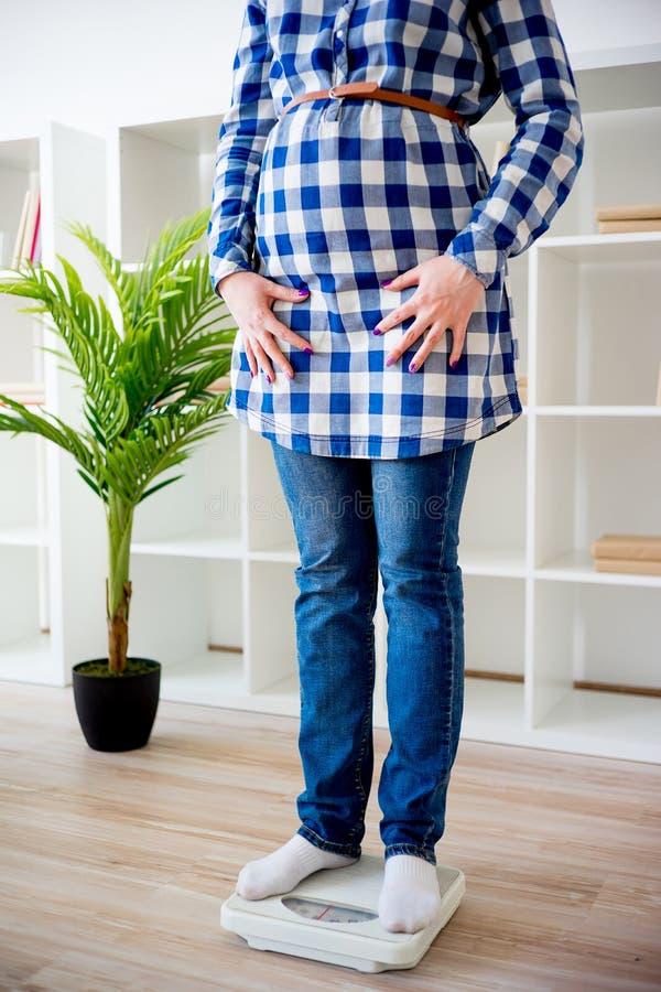 Беременная женщина проверяя вес стоковые фотографии rf