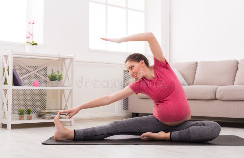 Беременная женщина протягивая тренировать внутри помещения стоковые изображения