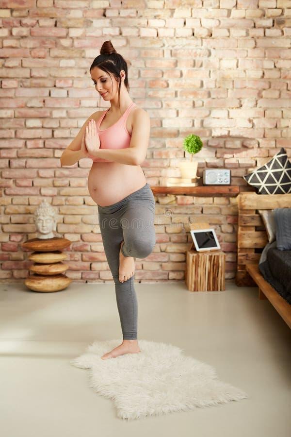 Беременная женщина работая дома в представлении йоги стоковая фотография rf