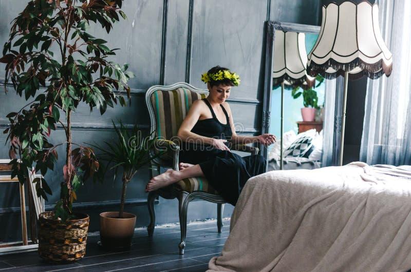 Беременная женщина сидит в кресле окном рядом с деревом Она смотрит заботливо на ее животе стоковые изображения rf