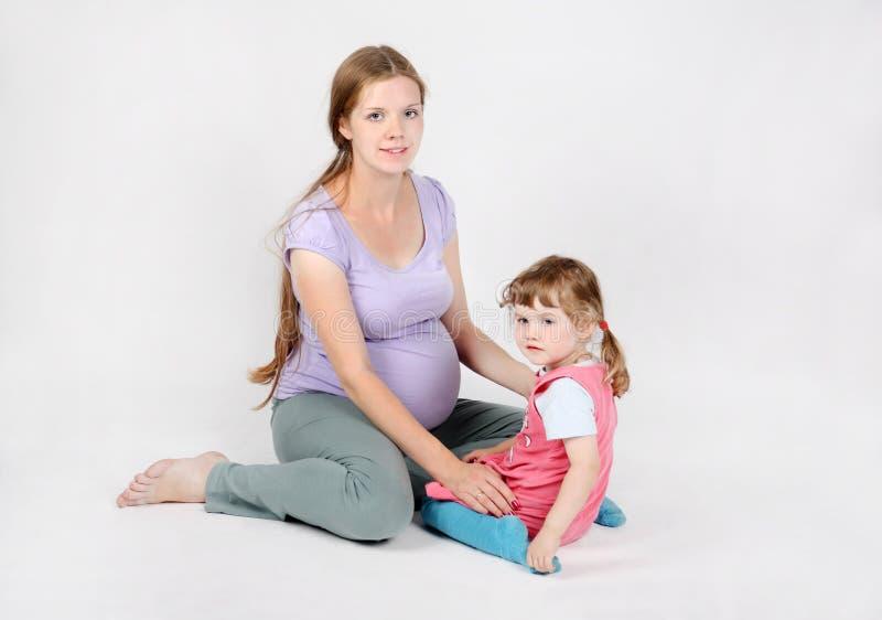 Беременная женщина сидит на поле с дочерью стоковая фотография rf