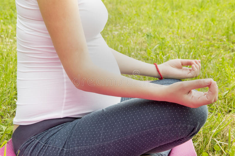 Беременная женщина сидя в положении и размышлять лотоса стоковое фото