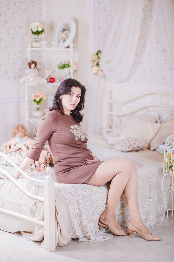 Беременная женщина сидя на кровати стоковая фотография