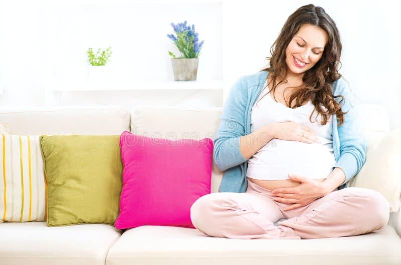 Беременная женщина сидя на софе стоковое изображение