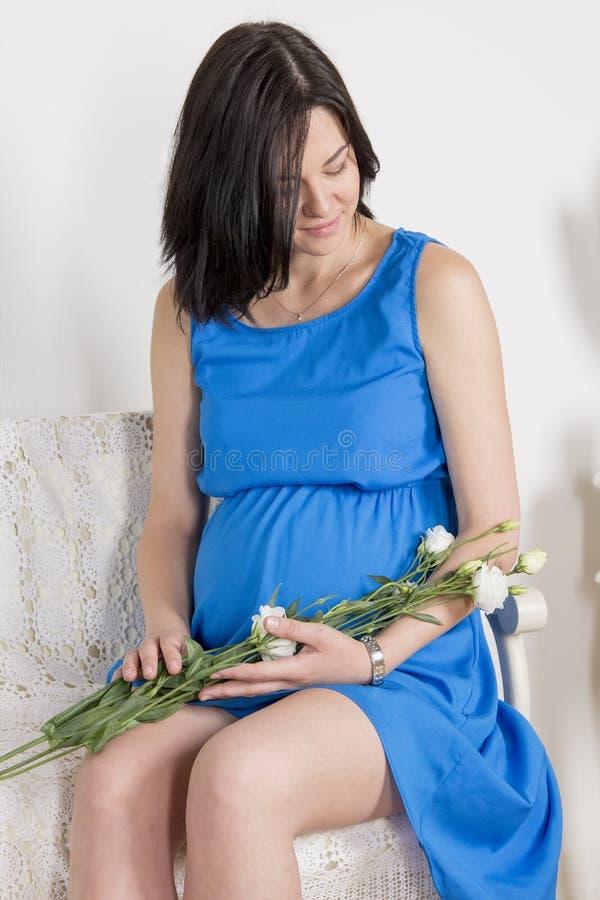 Беременная женщина сидя около кроватки стоковое изображение rf