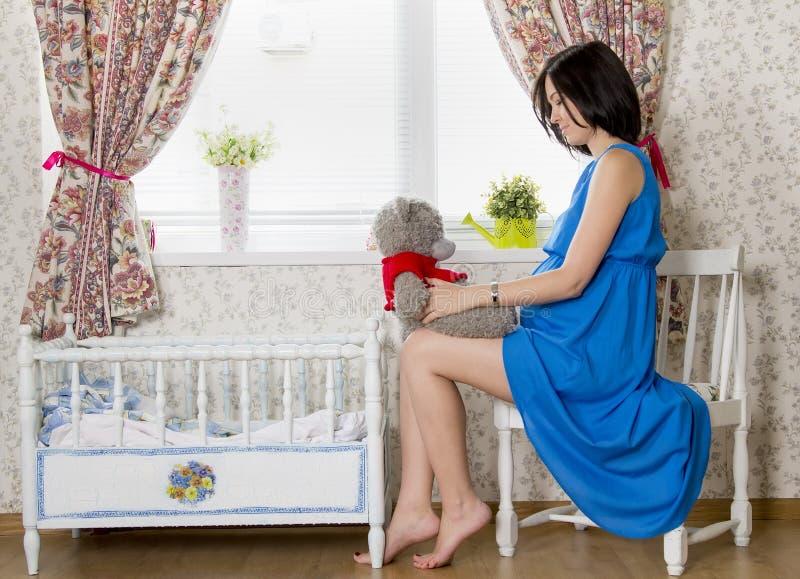 Беременная женщина сидя около кроватки стоковое фото