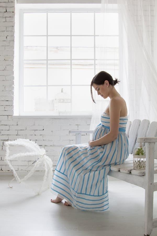 Беременная женщина сидя около окна стоковые изображения