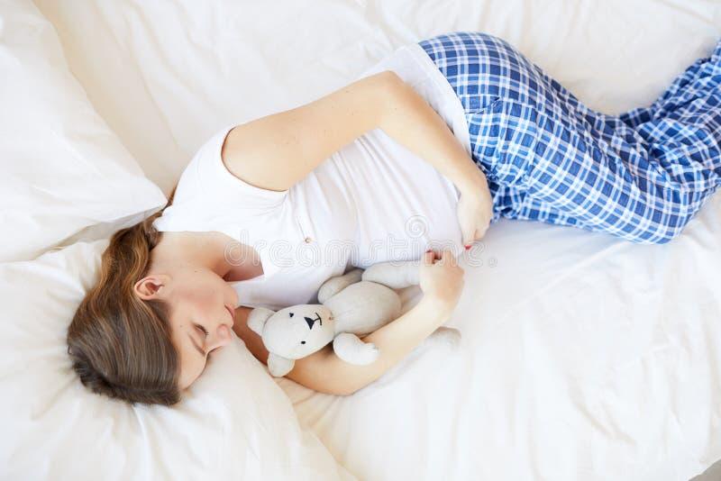 Беременная женщина спать в кровати стоковые фото