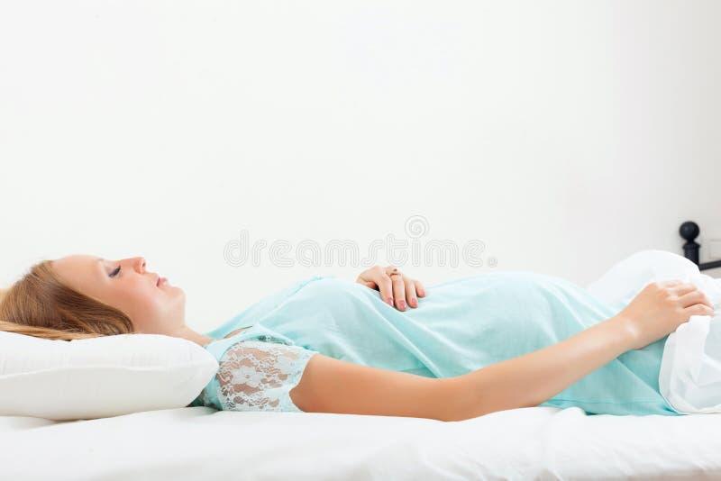 Беременная женщина спать на белом листе стоковая фотография