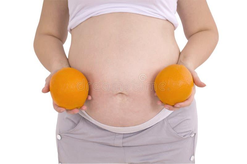 Беременная женщина с апельсином (путь клиппирования) стоковые изображения