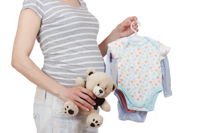 Беременная женщина с различными покрашенными одеждами для newborn и плюшевым мишкой в руке стоковые фотографии rf