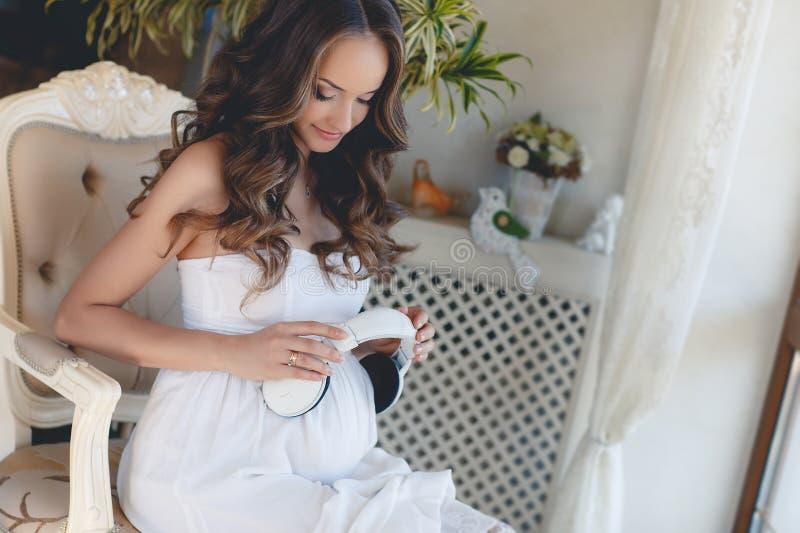 Беременная женщина слушая к вашей любимой музыке стоковые изображения
