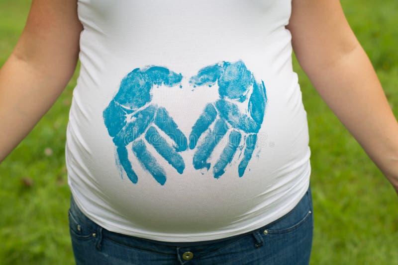 Беременная женщина с handprints на рубашке стоковое фото rf
